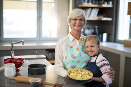 Grandmother and granddaughter posing with fresh cut apples on crust while making apple pie