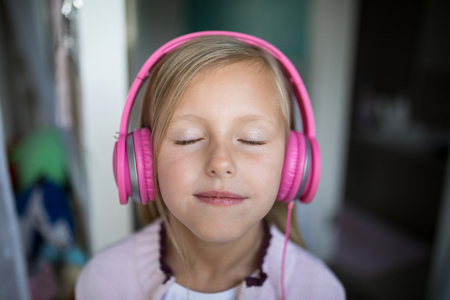 Close-up of girl listening to music on headphones at home