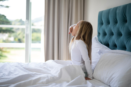 Girl yawning while waking in bed at home