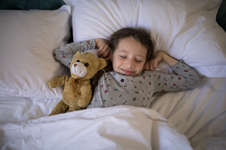 Girl sleeping on bed with teddy bear in bedroom at home Banco de Imagens