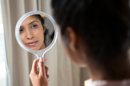 Młoda kobieta, zastanawiając się nad ręcznym lustrem w domu