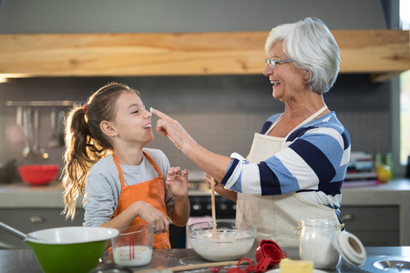 Grandmother putting flour on granddaughters nose in the kitchen Stock Photo