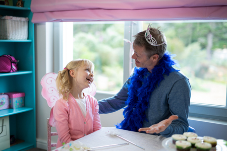 Smiling girl pretending to be a fairy playing with her father