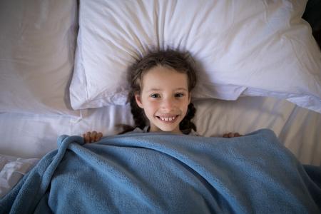 Portrait of smiling girl lying on bed in bedroom Banco de Imagens