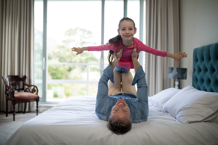 Smiling father lifting her daughter on the bed at home