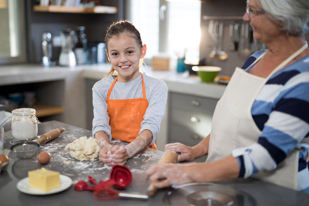 Granddaughter posing while kneading dough in the kitchen with grandmother Stock Photo