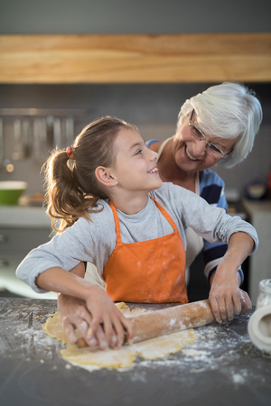Grandmother and granddaughter looking at each other while flattening dough in the kitchen