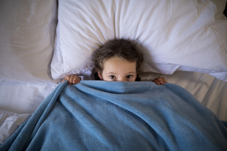 Portrait of girl covering her face under the blanket while lying on bed