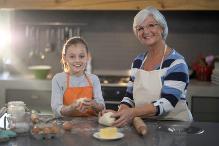 Grandmother and granddaughter kneading dough in the kitchen