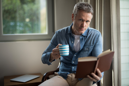 living wisdom: Portrait of man reading book while having coffee in living room at home
