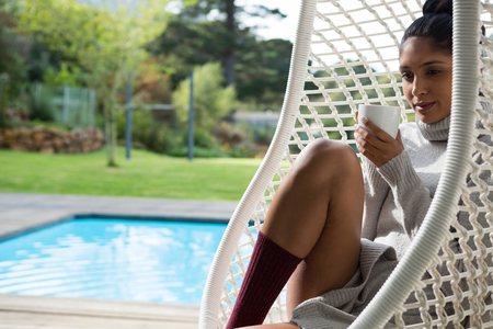 Young woman with coffee cup resting in swing chair at poolside