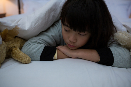 Girl with toys lying down on bed at home Stock Photo