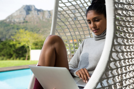 Woman using laptop while relaxing on swing chair at poolside Stock Photo