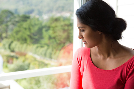 Thoughtful young woman looking through window at home