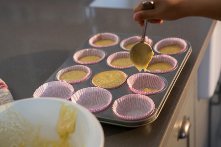 Cropped hand pouring batter in cupcake holder at kitchen counter