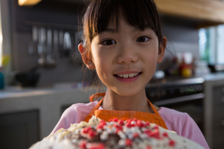 Close-up portrait of girl with cake in kitchen at home