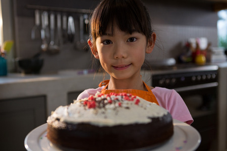Portrait of girl with cake standing in kitchen at home Stock Photo