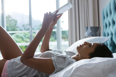 Young woman using digital tablet while relaxing on bed at home Stock Photo
