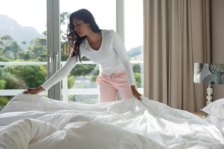 Young woman making bed at home