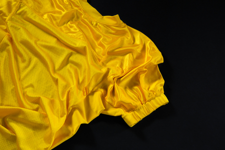 Close-up of American football jersey fabric against black background