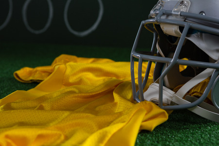 Close-up of American football head gear and jersey lying on artificial turf against strategy board Reklamní fotografie