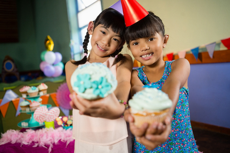 Portrait of kids having cupcake during birthday party at home