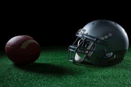 Close-up of American football head gear and football on artificial turf Stock Photo