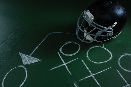 Close-up of American football head gear lying on green board with strategy drawn on it Reklamní fotografie
