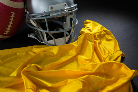 messed: Close-up of American football jersey, head gear and football against black background Stock Photo