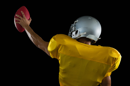 Rear view of American football player holding a ball high in one hand