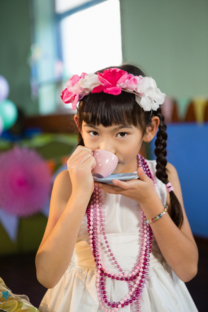 Portrait of cute girl drinking tea during birthday party at home
