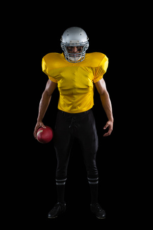 Portrait of American football player holding a ball in one hand