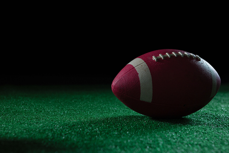 Close-up of American football on artificial turf against black background Reklamní fotografie