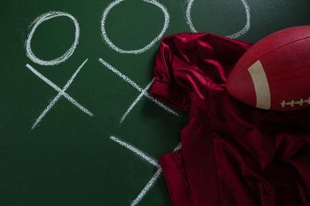 Close-up of American football jersey and football lying on green board with strategy drawn on it Reklamní fotografie