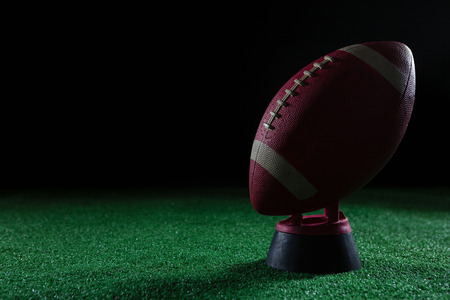 Close-up of American football standing on holder on artificial turf against black background Stock Photo