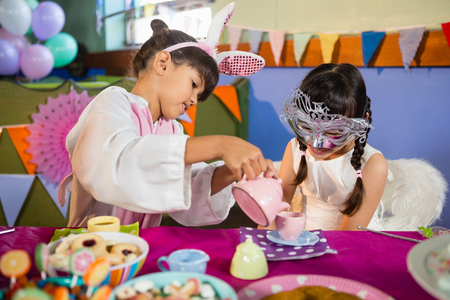 Kids playing with tea set during birthday party at home