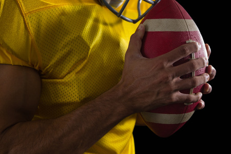 Mid section of American football player holding a ball with both his hands Reklamní fotografie