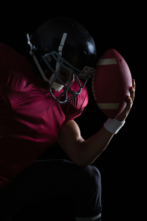 American football player sitting holding a ball in his hand against a black background