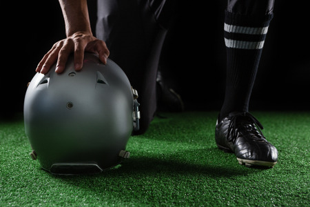 Close-up of American football player resting his hands on head gear kept on artificial grass