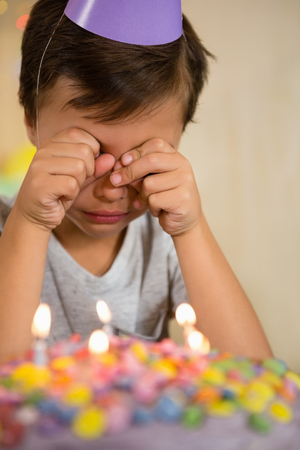 Upset boy sitting in front of birthday cake at home