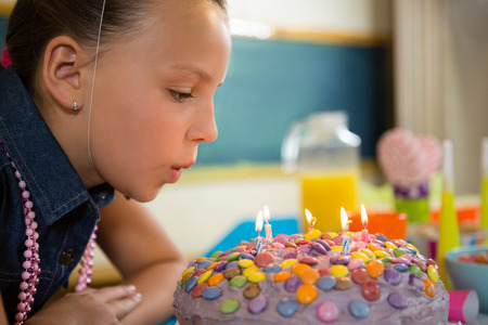 Girl blowing out the candles on a birthday cake at home