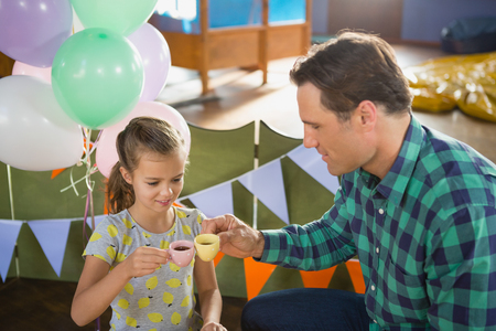 Smiling father and girl toasting their tea cups while playing with toy kitchen set Stock Photo