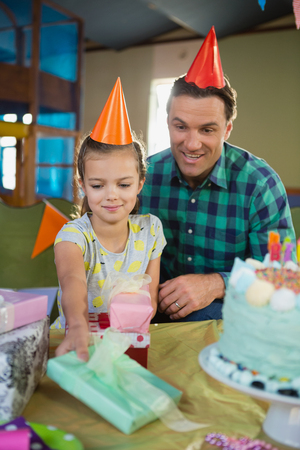 domicile: Smiling father and daughter in party hat looking gift box at home