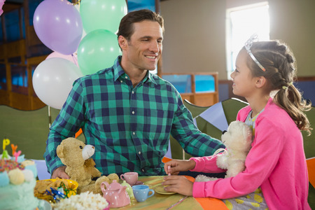 Father and girl interacting while playing toy kitchen set at home