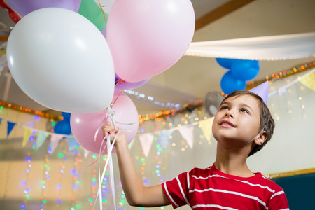 Cute boy holding colorful balloons during birthday party at home
