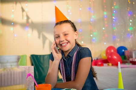 house call: Girl talking on mobile phone during birthday party at home