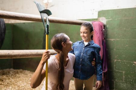 Smiling female jockey holding rake while talking to sister in stable
