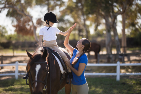 Side view of woman giving high five to girl sitting on horse in paddock Stockfoto