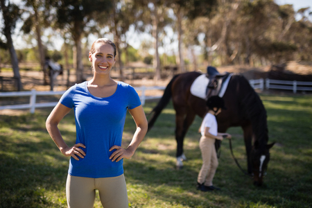 Portrait of female jockey with sister by horse in background at paddock