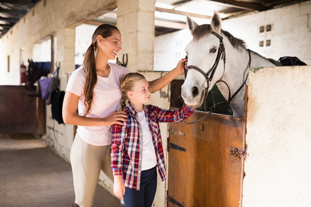Smiling sisters stroking horse while standing in stable
